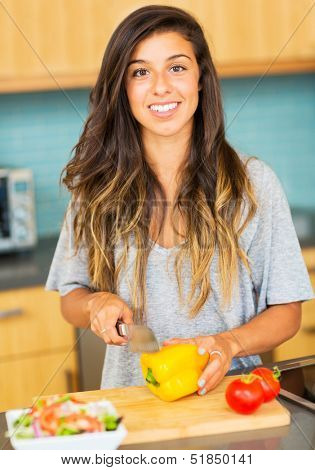 Beautiful young woman cutting vegitables, preparing healthy dinner at home