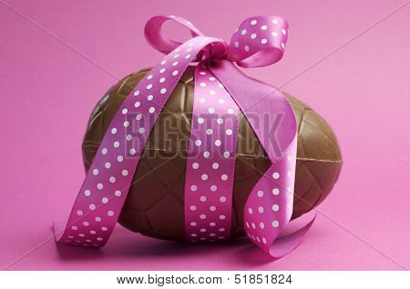 Large Happy Easter Chocolate Easter Egg With Pink Polka Dot Ribbon Tied In A Bow Against A Pretty Fe