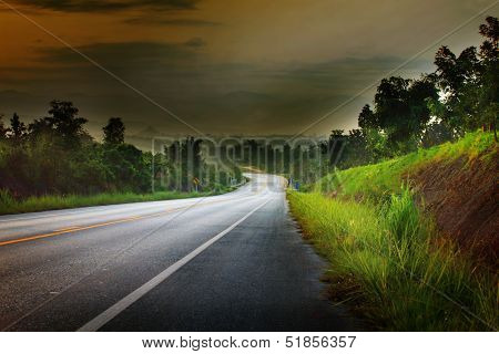 Asphalt Road Run Into The Mountain In Morning Light With Little Fog Adn Dramatic Sky