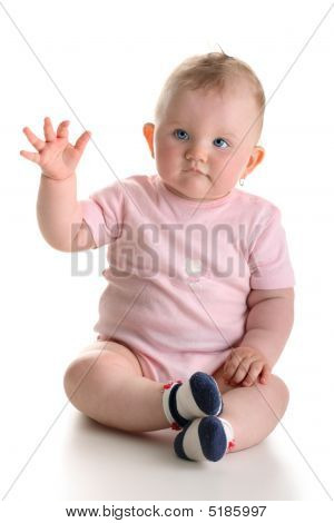 Sweet baby girl sitting and waving arm isolated with shadow