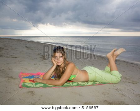 Beautiful Lady Relaxing And Smiling In The Beach, Laying On A Towel