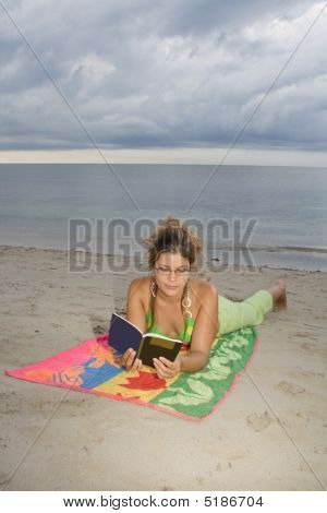 Girl With Glasses Reading A Book In The Beach