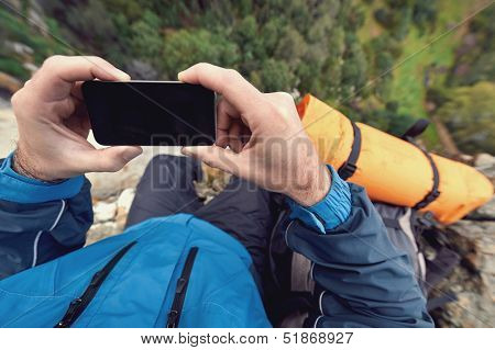 Adventure man with gps device or phone outdoors in wilderness exploring