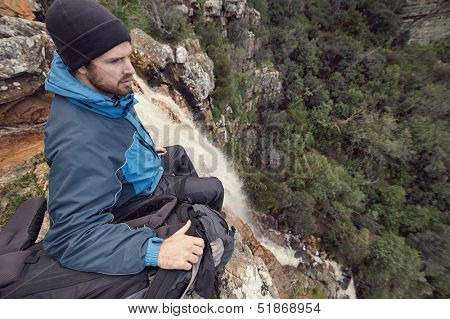 Man sitting on cliff edge looking at vie on outdoor lifestyle adventure hike