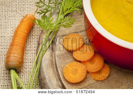 carrot cream soup in a  stoneware bowl on canvas background with carrot slices