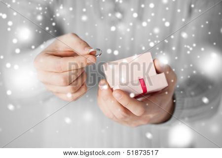 valentine's day, christmas, x-mas, winter, happiness concept - man holding wedding ring and gift box