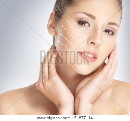 Close-up portrait of young, beautiful and healthy woman with arrows on her face (spa, surgery, face lifting and make-up concept)