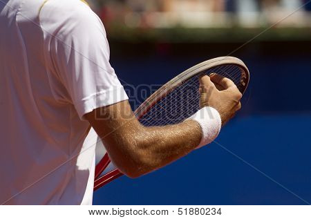 A tennis player checks racquet for serve a tennis ball during a match