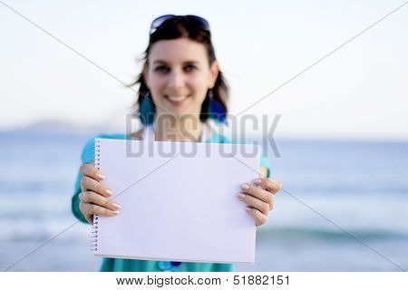 woman holding a paper at the beach