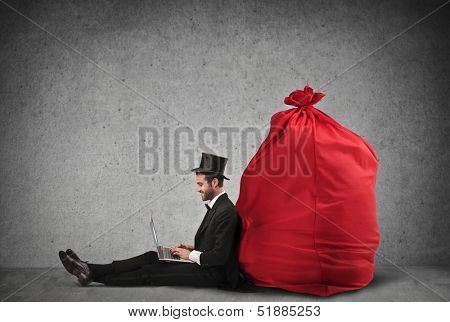 very rich businessman sitting on the floor working with laptop