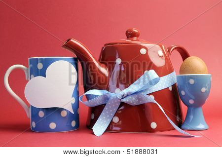 Red, White And Blue Breakfast With Polka Dot Tea Pot, Cup Mug, And Egg In Egg Cup Against A Red Back