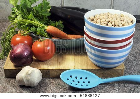 Vegetarian Cooking Concept With Eggplant, Carrots, Tomatoes, And Red Onion With Dried Chick Peas And