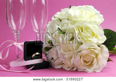 Wedding Bridal Bouquet Of White Roses On Pink Background With Pair Of Champagne Flute Glasses And Wo