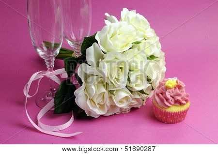 Wedding Bridal Bouquet Of White Roses On Pink Background With Pink Cupcake And Pair Of Two Champagne