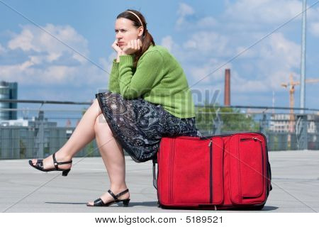 A Woman On A Suittase Looking Sad