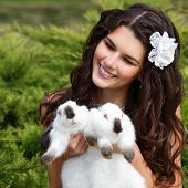 stock photo of alice wonderland  - Young woman bride smiling and holding two cute rabbits over park summer nature outdoor - JPG
