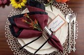 image of doilies  - Beautiful Thanksgiving table setting with lace doily place setting and fine bone china with vintage silverware red and black napkins on dark mahogany wood table with autumn pumpkin grapes and sunflower decorations - JPG
