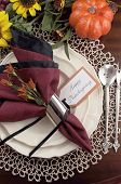 stock photo of doilies  - Beautiful Thanksgiving table setting with lace doily place setting and fine bone china with vintage silverware red and black napkins on dark mahogany wood table with autumn pumpkin grapes and sunflower decorations - JPG