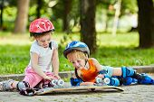 Little boy and girl in roller equipment sit on walkway in summer park and look upon upturned skatebo