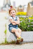 Little girl sits on granite curb of flower bed  on square