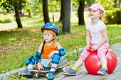 pic of skateboarding  - Little boy in protective equipment sits on skateboard and little girl sits on red ball for jumping on walkway in summer park - JPG