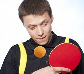 Young man playing ping pong against a blue background