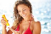 woman applying suntan lotion at the beach smiling
