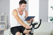 Smiling sporty man exercising on bike and using tablet in bright living room
