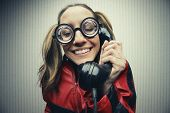 stock photo of nerds  - funny nerd humor woman talking retro vintage black telephone on vintage wallpaper - JPG