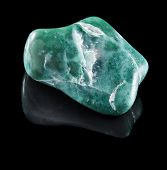 Jadeite mineral stone close up  with reflection on black surface background
