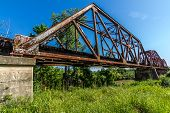 stock photo of trestle bridge  - An Interesting View of an Old Iconic Iron Truss Railroad Bridge Over the Brazos River - JPG