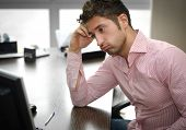 image of disappointment  - Tired or frustrated young man working in office looking at computer screen