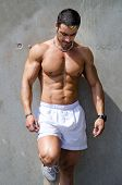 Muscular Male Bodybuilder Standing Against Wall Outdoors