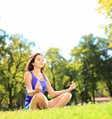 foto of stressless  - Young female athlete in sportswear meditating seated on a green grass in a park - JPG