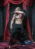 foto of fallen  - Fit Male Model with black wings on bed