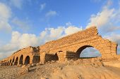 stock photo of aqueduct  - Roman aqueduct beach at sunset - JPG
