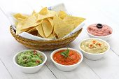 stock photo of crisps  - tortilla chips with four super bowl dips which are salsa roja - JPG