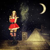 image of red roof  - beautiful sexy christmas fairy woman in red dress and in santa hat stay on tiled roof of house at magic night - JPG