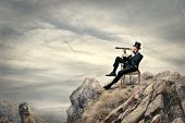 image of spyglass  - rich businessman sitting on a chair in the mountain looking the landscape with spyglass - JPG
