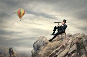 stock photo of spyglass  - rich businessman sitting on a chair in the mountain looking the landscape with spyglass - JPG