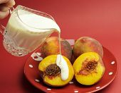 stock photo of peach  - Peaches and Cream Complexion concept with plate of fresh yellow peaches with pouring glass crystal jug of cream against a red background - JPG