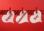stock photo of peg  - Happy Valentines Day message greeting written across white heart tags hanging from red pegs on a line for Valentines Day February 14 - JPG