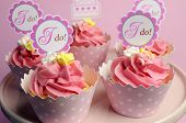 stock photo of cake stand  - Pink wedding cupcakes with I Do topper signs on pink cake stand  - JPG