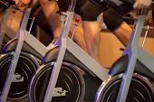 stock photo of cardio exercise  - Group of four people spinning in the gym - JPG