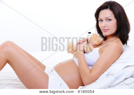 Smiling Young Pregnant Female Embrace The Teddy Toy