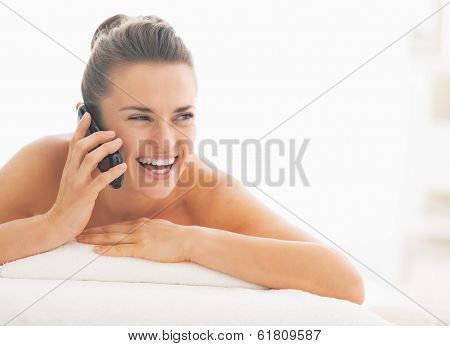 Young Woman Laying On Massage Table And Talking Mobile Phone