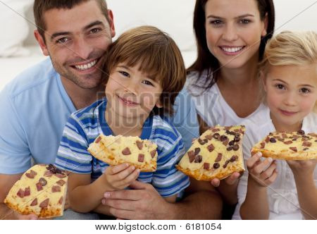 Portrait Of Family Eating Pizza On Sofa