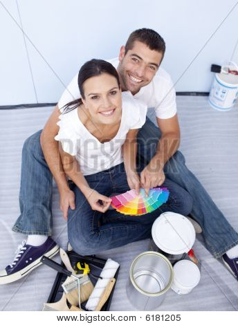 High Angle Of Couple Choosing Colours To Paint New House