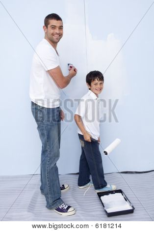 Happy Father And Son Painting A Wall