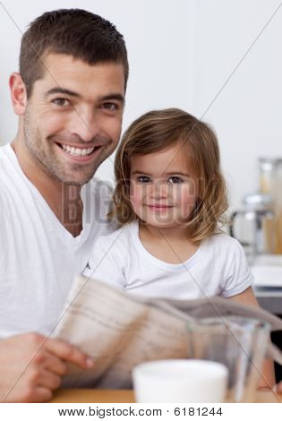 Smiling Father Reading A Newspaper With His Daughter